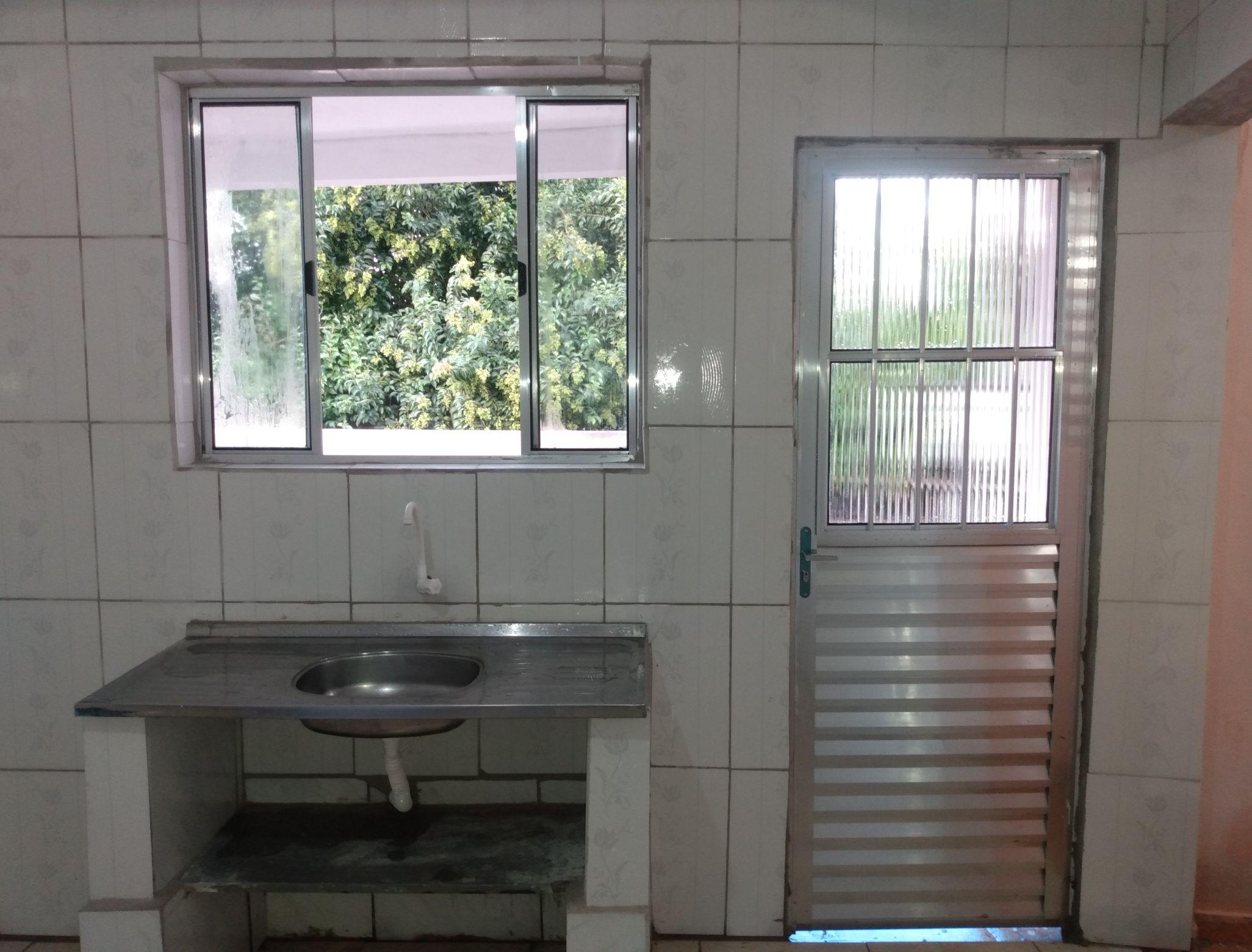 Bancada de pia feita de tijolo,azulejo e janela.