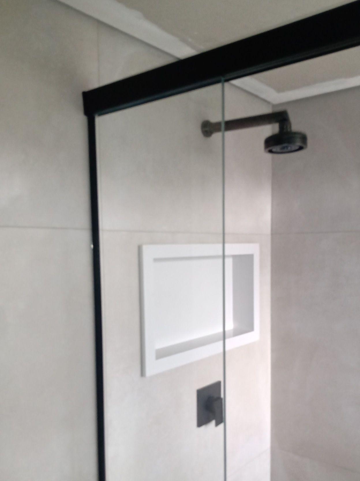 banheiro em porcelanato e nicho em mármore.